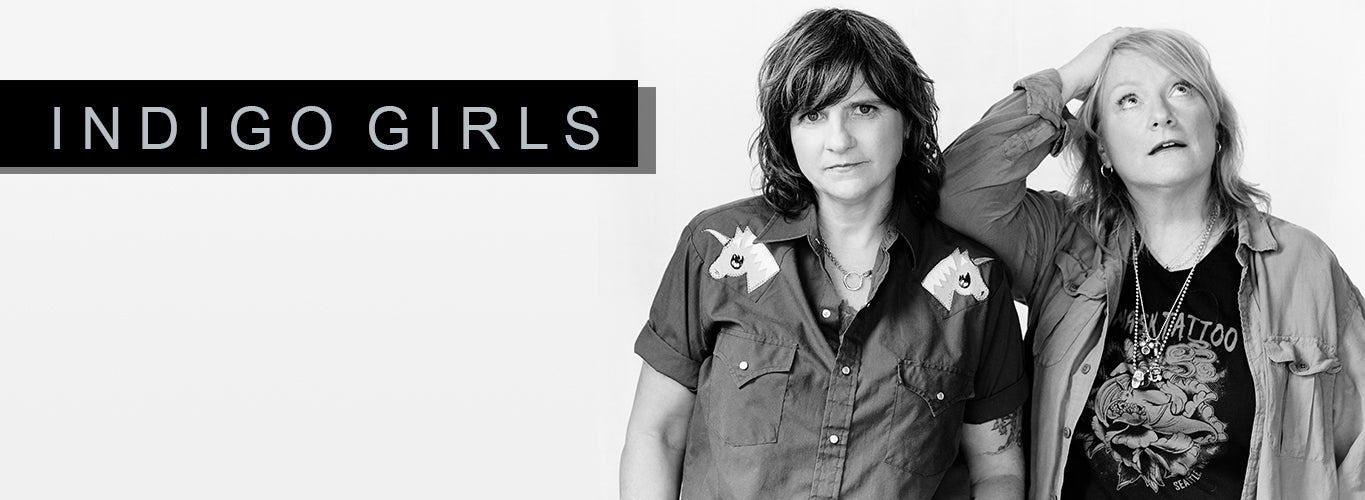 """Indigo Girls"" in white text on a black background, overlaid over a black and white image of Amy Ray and Emily Saliers."